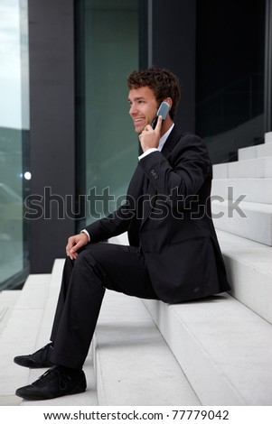 business man siting on stairs with telephone