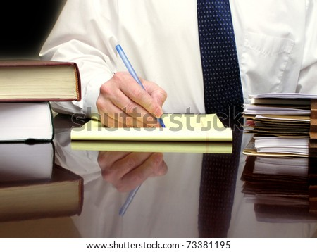 Business Man sitting at desk holding pen with files