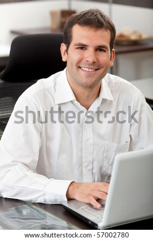 Business man sitting at her desk in the office with a laptop