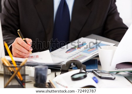 Business man sitting at office desk and working  with  documents. Close -up.