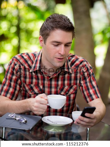 Business man sitting at table in cafe using mobile phone
