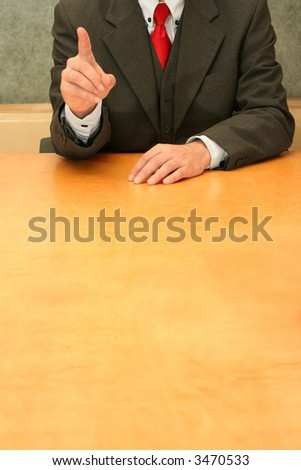 Business-man sitting at the desk, gesturing with his hand.