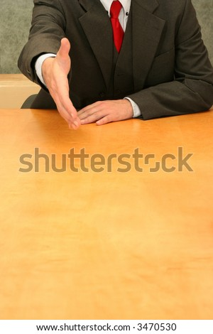 Business-man sitting at the desk wanting to shake your hand.