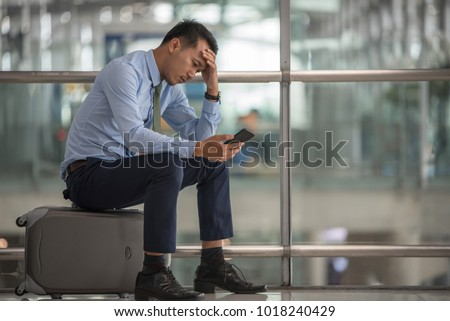 Business man sitting at the terminal airport, left hand touch at head, headache,right hand holding smarat phone,waiting traveling,flight delay ,selective focus,traveling concept, copyspace