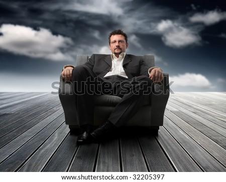 business man sitting on armchair  against a sky