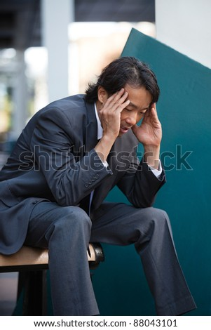 Business man sitting on bench outdoors not feeling well