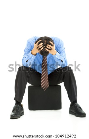 business man sitting on briefcase with headache