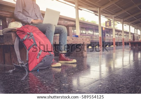 Business man sitting with using laptop. travel bag at the train station.vintage filter effected. side view. - Shutterstock ID 589554125