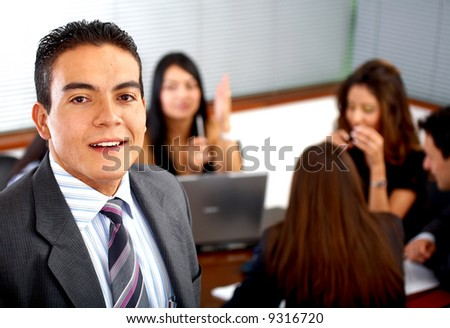 business man smiling leading a team during an office meeting
