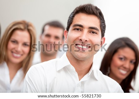 Business man smiling with a group behind at the office