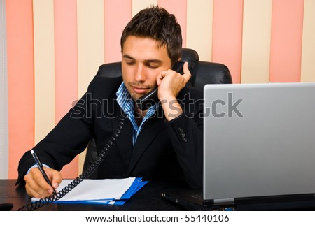 Business man speaking at telephone and taking notes on paper in his office - stock photo