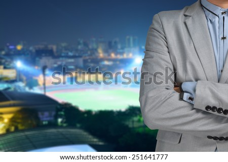 Business man sport manager and executive with background of soccer ball athletic stadium and race track