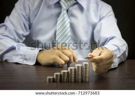 business man stacked coins on dark wood background, concept as investor, finance and capital banking   - Shutterstock ID 712973683