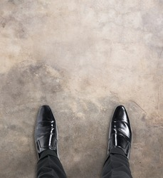 Business man standing at the beginning of a journey looking down at his feet