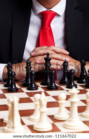 Business man standing in front of unstarted chess game