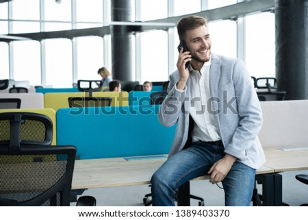Business man standing inside office building and using cell phone #1389403370