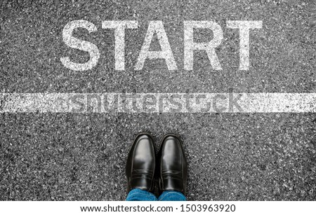 Business man standing on grunge concrete with white race line beginning idea. Top view. Feet and black shoes with word start written for concept on tarmac road background. Businessman challenge. Stockfoto ©