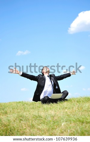 Business man standing on laptop in nature