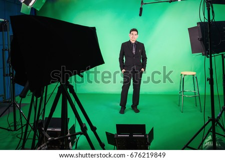 Business man standing up in front of the camera in television studio , Business man presenter in television Studio #676219849