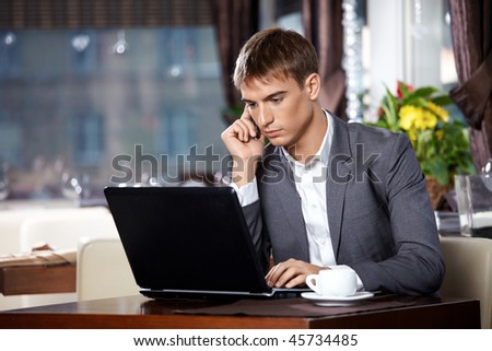 Business man talks to the laptop on mobile in cafe