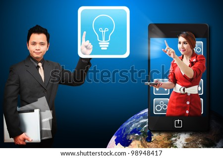 Business man touch Light Bulb icon from mobile phone : Elements of this image furnished by NASA - stock photo