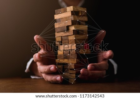 business man try to build wood block on wooden table and black background business organization startup concept