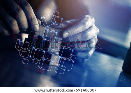 business man try to build wood block on wooden table and blur background business  organization startup concept