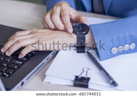 Business man typing on the keyboard and watching at his wristwatch. Time is up. Concept of Time Management, Work Life Balance and Business Control.
