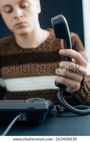 Business man using a black telephone in the office