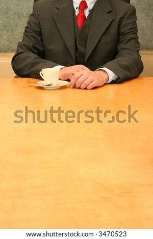 Business-man waiting at the desk, cup of coffee.