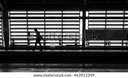 Business man walking around the train station alone