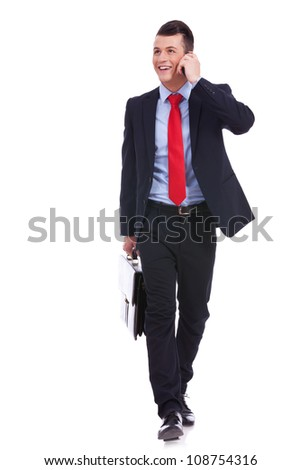 Business man Walking forward and looking to a side while talking on the phone and carying a briefcase over white background