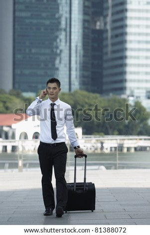 Business man Walking with a wheeled Suitcase on phone