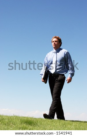 Business man walking with laptop in hand across the green grass and blue sky