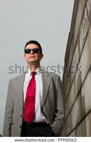 Business man wearing black sunglasses with light grey suit and red tie walking on the street near brick wall. Industrial environment.
