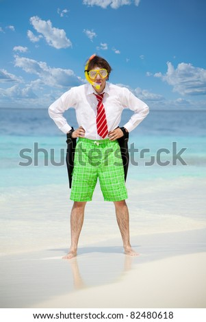 Business man wearing white shirt  and tie and also scuba, mask and holding flippers on the beach in angry pose