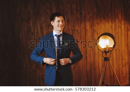 Business man wears blue jacket. The groom. In the background is a retro lamp. The walls are of dark wood #578303212