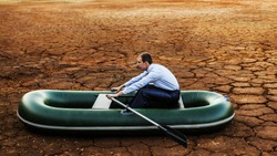 Business man will rows home for shore in paddle powered row boat businessman in boat rocks looks bright future symbol crisis stagnation losses braking environmental disaster water scarcity drought
