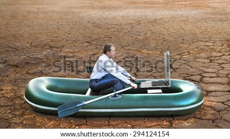 Business man will rows home for shore in paddle powered row boat in boat looking at  laptop rocks looks future symbol crisis losses braking difficulties environmental disaster water scarcity drought