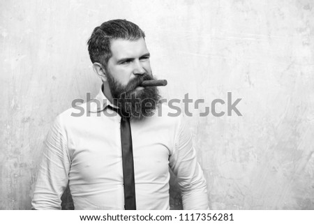 business man with a cigar. bearded man or hipster with long beard and stylish hair on serious face in tie and white shirt on textured beige background smoking cigar, copy space #1117356281