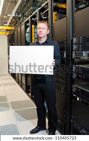 Business man with a contemplative look holding a white board in a datacenter.