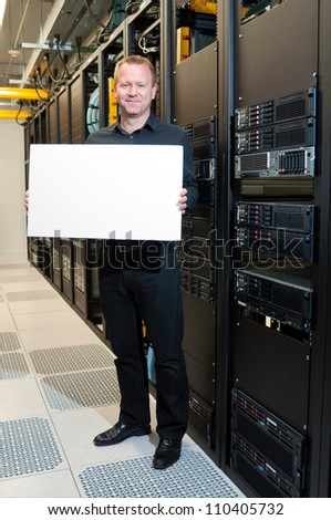 Business man with a satisfied look holding a white board in a datacenter.