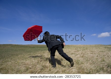 Business man with an open umbrella on the meadow