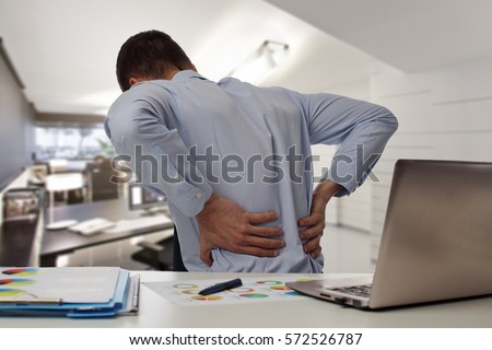 Photo of  Business man with back pain an office . Pain relief concept