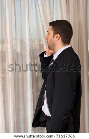 Business man with cellhone looking through window to cityscape