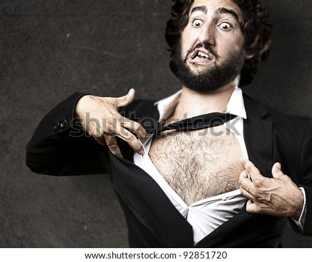 business man with courage and superman concept tearing off his shirt against a grunge wall