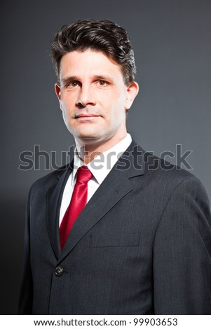 Business man with dark grey suit and red tie isolated on dark background. Studio shot.