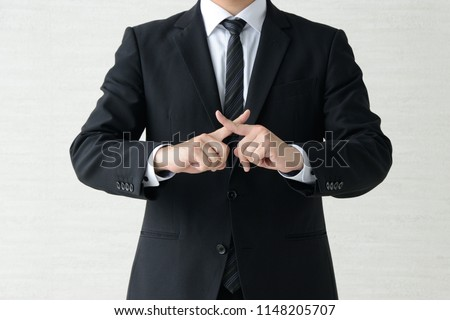 Business man with fingers crossed #1148205707