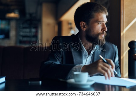 business man with glasses thinks looks out the window, cafe, documents, cup of coffee