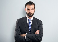 Business man with his arms crossed over textured background